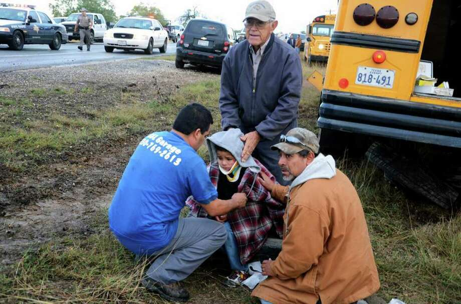 Jourdanton ISD bus driver Joe Lopez, kneeling at right, and Willie Cordova, standing and facing the camera, help an unidentified man talk to student John Cape at the scene of a fatal accident. Cape was a passenger on the school bus. A Jourdanton ISD bus sits by the road after it was involved in a three-vehicle accident Monday morning. Photo: JACK GARCIA, FOR THE EXPRESS-NEWS