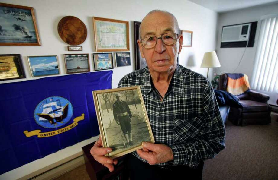 CHARLIE NEIBERGALL : ASSOCIATED PRESS  LONG VOYAGE: Clarence Pfundheller, of Greenfield, Iowa, shows a photo of himself taken during Navy basic training in 1939. Now 91, Pfundheller will be returning to Pearl Harbor on Wednesday to honor those lost and share stories about the war. Photo: Charlie Neibergall / AP