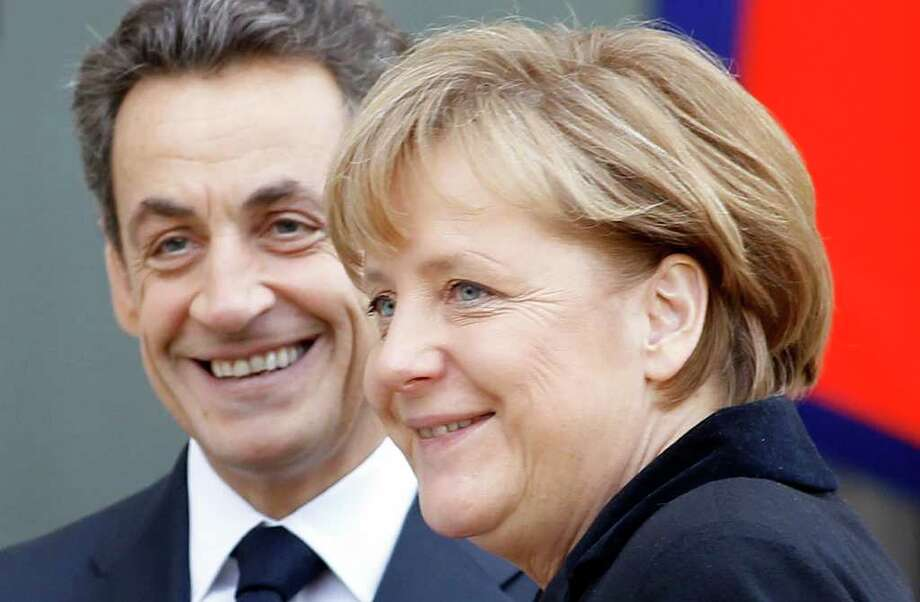 French President Nicolas Sarkozy, left, smiles as he greets German Chancellor Angela Merkel prior to their meeting at the Elysee Palace in Paris, Monday Dec. 5, 2011. The leaders of Germany and France will try to agree Monday on a cohesive plan to help save the euro through stricter oversight of government budgets. Financial markets signaled optimism that French President Nicolas Sarkozy and German Chancellor Angela Merkel will unveil a unified plan that tightens political and economic cooperation among the 17 European Union countries that use the euro and sets the stage for more aggressive aid from the European Central Bank. (AP Photo/Remy de la Mauviniere) Photo: Remy De La Mauvinere / AP