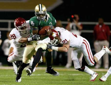 Baylor quarterback Robert Griffin, center, is brought down by Oklahoma defenders Travis Lewis (28) and Tom Wort (21) on a run in the first half of an NCAA college football game, Saturday, Nov. 20, 2010, in Waco, Texas. Photo: AP