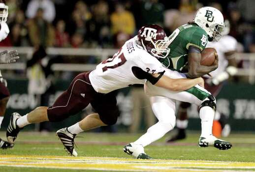 Texas A&M linebacker Michael Hodges (37) makes a tackle on Baylor quarterback Robert Griffin III (10) in the second quarter of an NCAA Big XII Conference football game between Baylor and Texas A&M at Floyd Casey Stadium on Saturday, Nov. 13, 2010, in Waco. Photo: Julio Cortez, Houston Chronicle / © 2010 Houston Chronicle