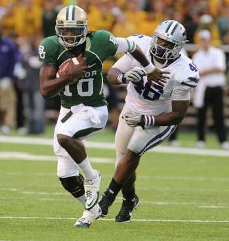 Baylor quarterback Robert Griffin, left, slips past Kansas State defensive tackle Prizell Brown during the first half of a NCAA football game, Saturday, Oct. 23, 2010, in Waco Texas. Photo: AP