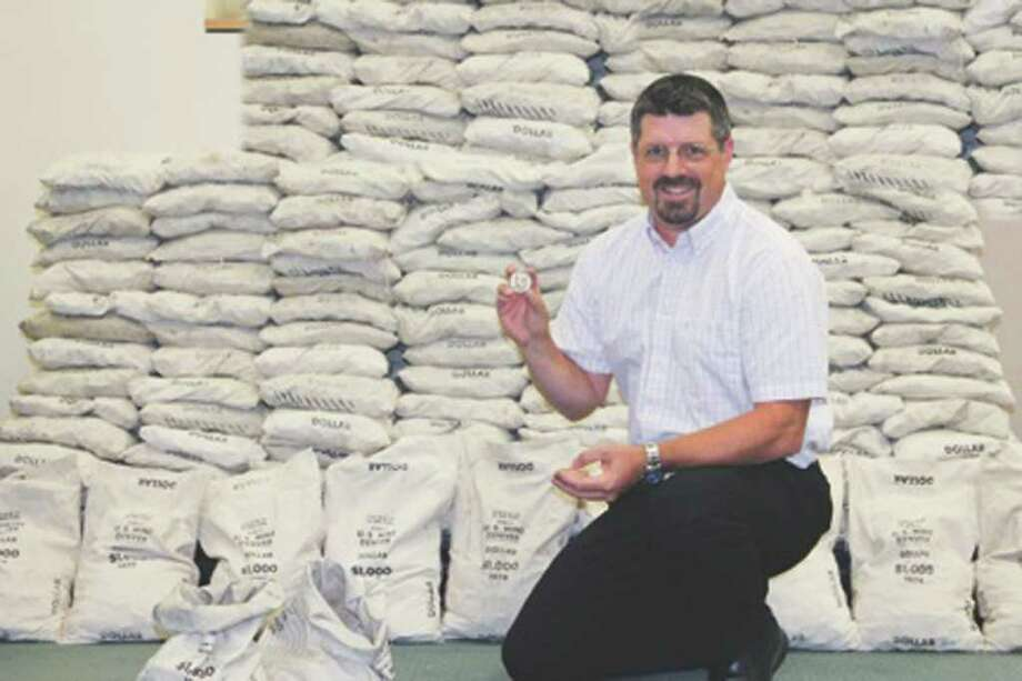 In this Aug. 2011 photo provided by the Littleton Coin Company, Ken Westover poses in front of bags of Eisenhower silver dollars at the company in Littleton, N.H. The company acquired nearly a quarter million of the silver dollars that had been sitting in a basement vault of a Montana bank for more than thirty years. (AP Photo/Littleton Coin Company, Stephanie Westover) Photo: Stephanie Westover / Littleton Coin Company