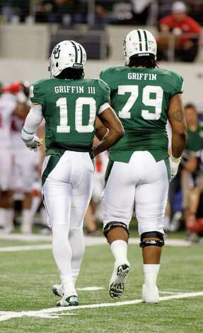 "In this Nov. 26, 2011, photo, Baylor quarterback Robert Griffin III (10) and right guard Robert T. Griffin (79) walk to the huddle during an NCAA college football game against Texas Tech in Arlington, Texas. Baylor's biggest player on the field has the initials RG and is referred to by teammates as ""Big Griff."" Yes, his name is Robert Griffin. But this isn't the Heisman Trophy hopeful quarterback for the Bears. He is the 6-foot-6, 330-pound right guard blocking for RG3. Photo: AP"