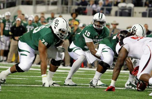 In this Nov. 26, 2011, photo, Baylor right guard Robert T. Griffin (79) and quarterback Robert Griffin III (10) get ready for a play during an NCAA college football game against Texas Tech in Arlington, Texas. Baylor's biggest player on the field has the initials RG and is referred to by teammates as ``Big Griff.'' Yes, his name is Robert Griffin. But this isn't the Heisman Trophy hopeful quarterback for the Bears. He is the 6-foot-6, 330-pound right guard blocking for RG3. Photo: AP
