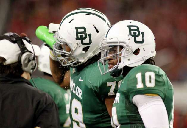 In this Nov. 26, 2011, photo, Baylor  right guard Robert Griffin (79) and quarterback Robert Griffin III (10) take a timeout during an NCAA college football game against Texas Tech in Arlington, Texas. Photo: AP