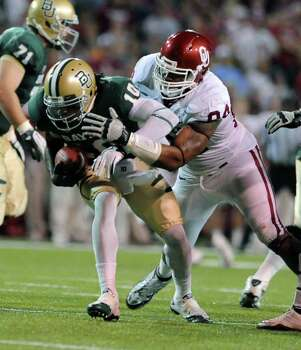Oklahoma's Frank Alexander, right, sacks Baylor quarterback Robert Griffin III, left, in the first half of an NCAA college football game, Saturday, Nov. 19, 2011, in Waco, Texas. Photo: AP