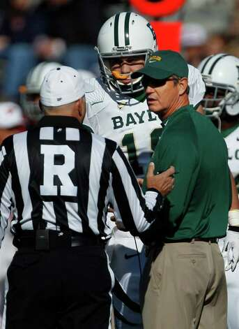 Baylor coach Art Briles, right, and quarterback Robert Griffin III, rear, talk with referee Cooper Castleberry during the first half of an NCAA college football game against Kansas in Lawrence, Kan., Saturday, Nov. 12, 2011. Photo: AP