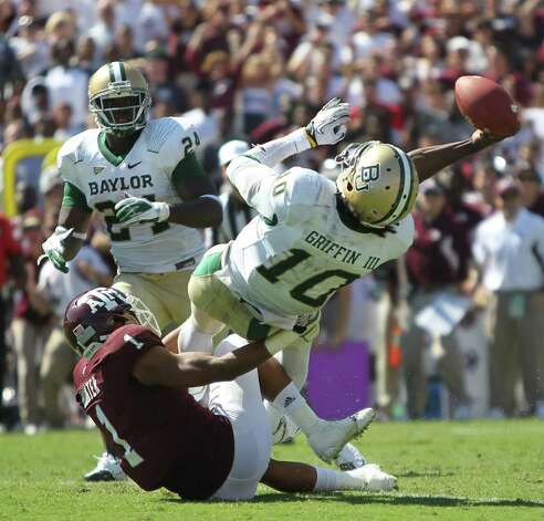 Texas A&M defensive back Trent Hunter (1) forces Baylor quarterback Robert Griffin III (10) to make a bad throw as he nearly sacks him during the fourth quarter of a NCAA football game at Kyle Field, Saturday, Oct. 15, 2011,  in College Station. Texas A&M won 55-28. Photo: Nick De La Torre, Houston Chronicle / © 2011  Houston Chronicle