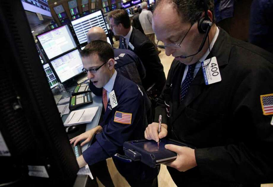 Specialist Bradley Kessler, left, and trader Gordon Charlop, right, work on the floor of the New York Stock Exchange Monday, Dec. 5, 2011. Stocks rose broadly in early trading Monday on hopes for a plan to restore long-term confidence in the euro. (AP Photo/Richard Drew) Photo: Richard Drew
