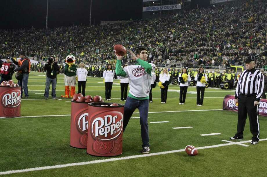 Jeremy Mehta of Niskayuna, a junior at SUNY Brockport, throws footballs at a two-foot replica of a Dr. Pepper can during halftime of Friday night's Pac-12 football championship game between UCLA and Oregon at Eugene, Ore. Mehta was successful on 15 attempts in 30 seconds to win $100,000 in scholarship money. Photo credit: Dr. Pepper