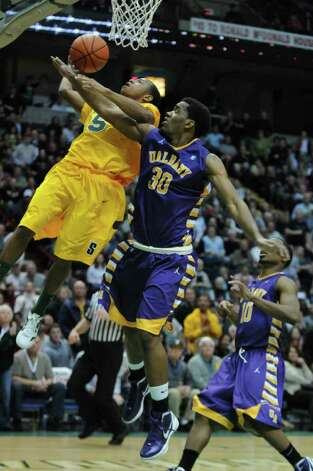 Siena's Evan Hymes is fouled by UAlbany's Jayson Guerrier near the end of Siena's 64-60 victory at the Times Union Center on Monday night Dec. 5, 2011 in Albany, NY.   (Philip Kamrass / Times Union ) Photo: Philip Kamrass / 10015374A