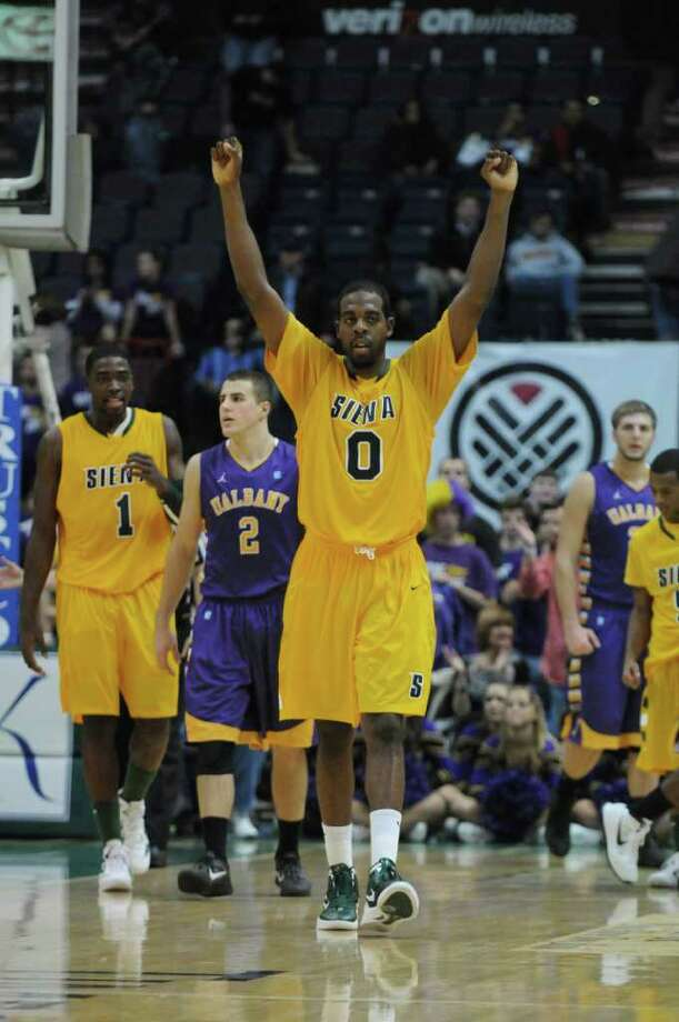 Siena's Brandon Walters celebrates near the end of the second half of their 64-60 win over UAlbany at the Times Union Center on Monday night Dec. 5, 2011 in Albany, NY.  Teammate OD Anosike is at left, while UAlbany's Logan Aronhalt is second from left. (Philip Kamrass / Times Union ) Photo: Philip Kamrass / 10015374A