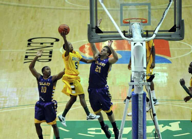Siena's Evan Hymes drives to the basket as UAlbany players Mike Black, left, and Blake Metcalf, righ
