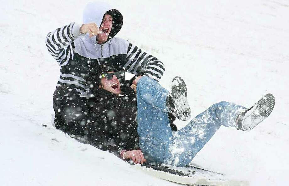 New Mexico State University sophomores Kirk Webber, left, and Wesley Levy smile as they successfully slide down the hill of Aggie Memorial Stadium in Las Cruces, N.M. on a plastic fold-up table, Monday, Dec. 5, 2011. Photo: Shari V. Hill, Associated Press / The Las Cruces Sun-News