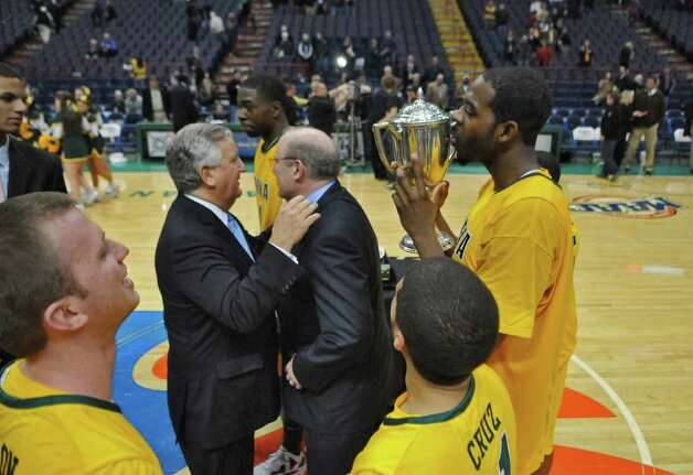 Siena's Brandon Walters kisses the Albany Cup after their 64-60 victory over UAlbany at the Times Union Center on Monday night Dec. 5, 2011 in Albany, NY.   Albany Mayor Gerald Jennings, left, congratulates Siena coach Mitch Buonaguro, center. (Philip Kamrass / Times Union ) Photo: Philip Kamrass / 10015374A