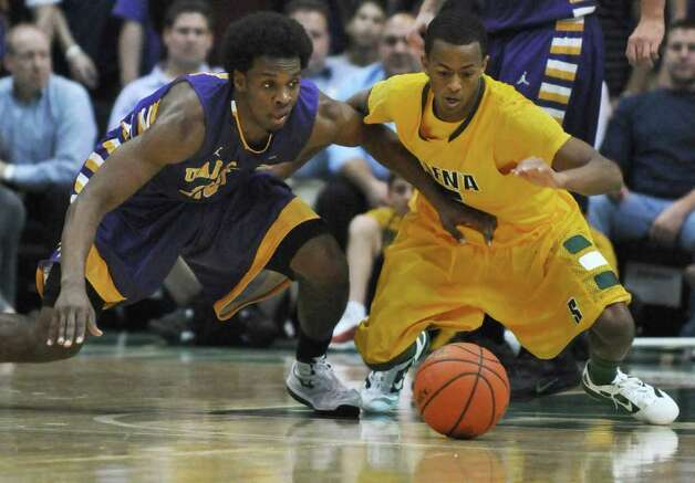 UAlbany's Gerardo Suero, left, and Siena's Evan Hymes battle for a loose ball during Siena's 64-60 victory at the Times Union Center on Monday night Dec. 5, 2011 in Albany, NY.   (Philip Kamrass / Times Union ) Photo: Philip Kamrass / 10015374A