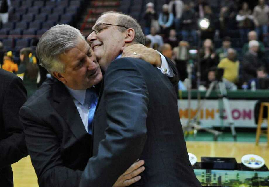 Albany Mayor Gerald Jennings, left, congratulates Siena coach Mitch Buonaguro, during the presentation of the Albany Cup after their 64-60 victory over UAlbany at the Times Union Center on Monday night Dec. 5, 2011 in Albany, NY.  (Philip Kamrass / Times Union ) Photo: Philip Kamrass / 10015374A
