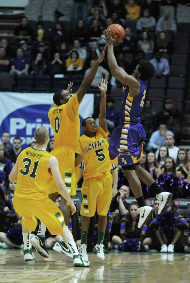 Siena's Owen Wignot, left, Brandon Walters and Evan Hymes, 5, defend UAlbany's Gerardo Suero during the second half of their 64-60 victory over UAlbany at the Times Union Center on Monday night Dec. 5, 2011 in Albany, NY.    (Philip Kamrass / Times Union ) Photo: Philip Kamrass / 10015374A