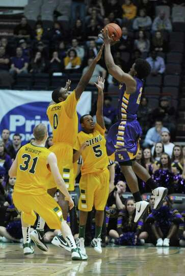 Siena's Owen Wignot, left, Brandon Walters and Evan Hymes, 5, defend UAlbany's Gerardo Suero during