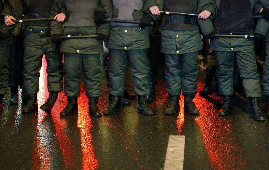 Red lights of police cars are reflected on the wet asphalt where police officers block the road after a political rally in downtown Moscow, Monday, Dec. 5, 2011. Several thousand people have protested in Moscow against Prime Minister Vladimir Putin and his party, which won the largest share of a parliamentary election that observers said was rigged. A group of several hundred then marched toward the Central Elections Commission near the Kremlin, but were stopped by riot police and taken away in buses. (AP Photo/Alexander Zemlianichenko) Photo: Alexander Zemlianichenko / Copyright 2011 The Associated Press. All rights reserved. This m