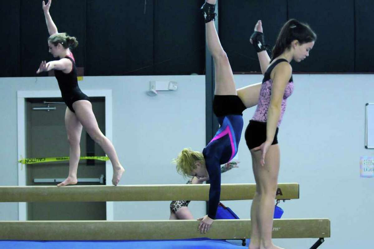 Saratoga Springs High School gymnasts Morgan Winnie, left, Lindsey Hartmann, center, and Rema Bianco, right, work out with teammates at the Saratoga Regional YMCA on Monday Dec. 5, 2011 in Wilton, NY. (Philip Kamrass / Times Union )