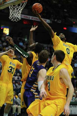 Siena's Brandon Walters gathers in a rebound over teammate OD Anosike during the first half of their 64-60 victory over UAlbany at the Times Union Center on Monday night Dec. 5, 2011 in Albany, NY.  (Philip Kamrass / Times Union ) Photo: Philip Kamrass / 10015374A