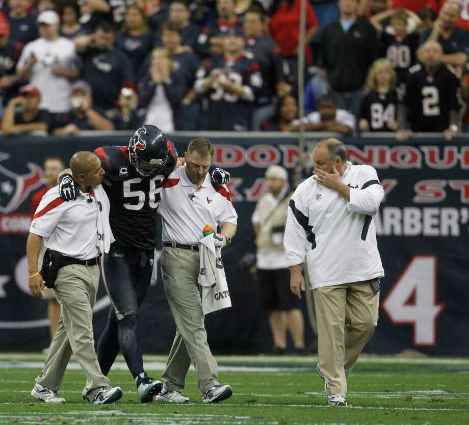KAREN WARREN: CHRONICLE WALKING WOUNDED: Texans linebacker Brian Cushing (56) is helped off the field in the second quarter Sunday after injuring his knee. He came back to play in the second half. Photo: Karen Warren / © 2011 Houston Chronicle