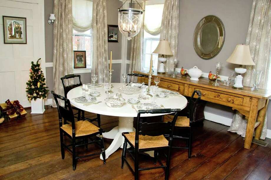 This dining room of the rectory of St. Paul's Church rhas been transformed by Maureen D'Avanzo Interior Design, of Southbury. This table started out as a pedestal-bototm kitchen table that had been left in the rectory for the annual church sale in June. D'Avanzo had this new, larger top made by Woodbury carpenter Ron Green, then had it lacquered with bright-white auto paint. Photo: Contributed Photo