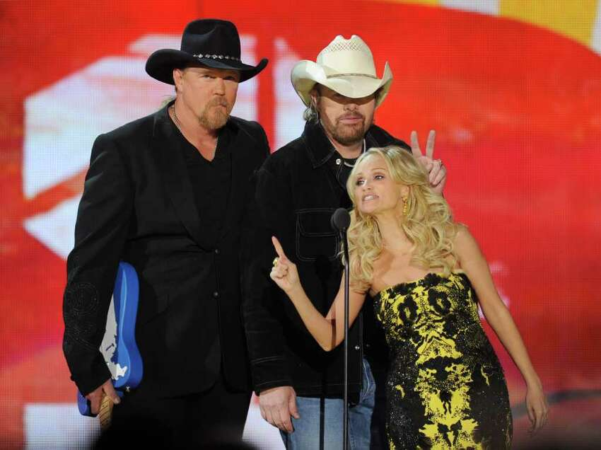 LAS VEGAS, NV - DECEMBER 05: Co-hosts Trace Adkins (L) and Kristin Chenoweth (R) present recording artist Toby Keith (C) with the Artist of the Decade award at the American Country Awards at the MGM Grand Garden Arena December 5, 2011 in Las Vegas, Nevada. (Photo by Ethan Miller/Getty Images)