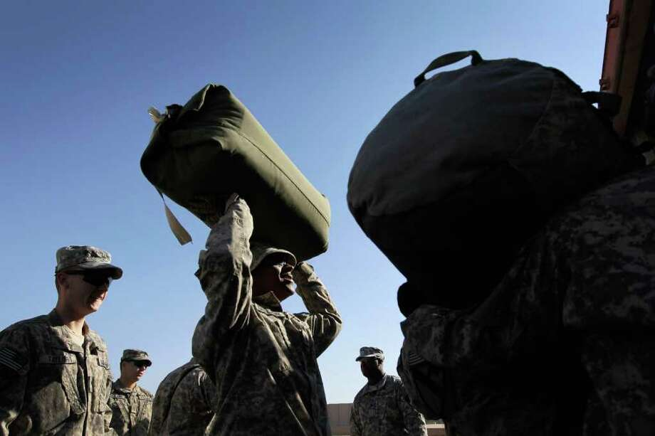 NASIRIYAH, IRAQ - DECEMBER 06:  U.S. Army Sergeant First Class Derek Bellamy from Philladelphia, Pennsylvania of the 2-82 Field Artillery, 3rd Brigade, 1st Cavalry Division, holds a bag as he waits to put it into a shipping container as they prepare to leave Camp Adder as the base is readied to be handed back to the Iraqi government later this month on December 6, 2011 at Camp Adder, near Nasiriyah, Iraq. Camp Adder is one of the few bases remaining that the United States controls as America's military continues its pullout of the country by the end of this year, after eight years of war and the overthrow of Saddam Hussein.  (Photo by Joe Raedle/Getty Images) Photo: Joe Raedle, Getty Images / 2011 Getty Images