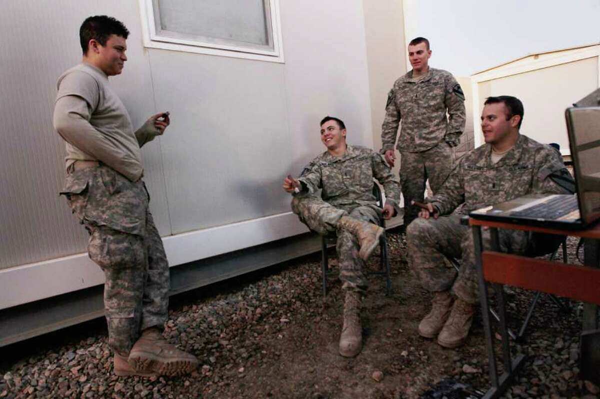 NASIRIYAH, IRAQ - DECEMBER 06: U.S. Army Private Steven Villalobos from Wheeling, Illinois, Lieutenant Christopher Molaro from Hawley, Pennsylvania, Lieutenant Adam Wilson from Ontario, California and Lieutenant Patrick Mulvaney from Sugar Land, Texas (L-R) of the 2-82 Field Artillery, 3rd Brigade, 1st Cavalry Division, smoke cigars and listen to music together as they wait for the orders to convoy to Kuwait from Camp Adder as the base is prepared to be handed back to the Iraqi government later this month on December 6, 2011 at Camp Adder, near Nasiriyah, Iraq. Camp Adder is one of the few bases remaining that the United States controls as America's military continues its pullout from the country by the end of this year after eight years of war. (Photo by Joe Raedle/Getty Images)