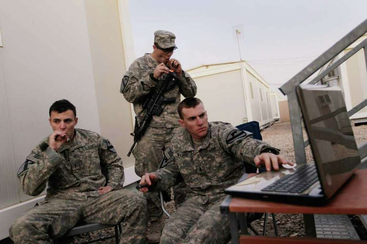 NASIRIYAH, IRAQ - DECEMBER 06: U.S. Army Lieutenant Christopher Molaro from Hawley, Pennsylvania, Lieutenant Patrick Mulvaney from Sugar Land, Texas and Lieutenant Adam Wilson from Ontario, California (L-R) of the 2-82 Field Artillery, 3rd Brigade, 1st Cavalry Division, smoke cigars and listen to music together as they wait for the orders to convoy to Kuwait from Camp Adder as the base is prepared to be handed back to the Iraqi government later this month on December 6, 2011 at Camp Adder, near Nasiriyah, Iraq. Camp Adder is one of the few bases remaining that the United States controls as America's military continues its pullout from the country by the end of this year after eight years of war. (Photo by Joe Raedle/Getty Images)