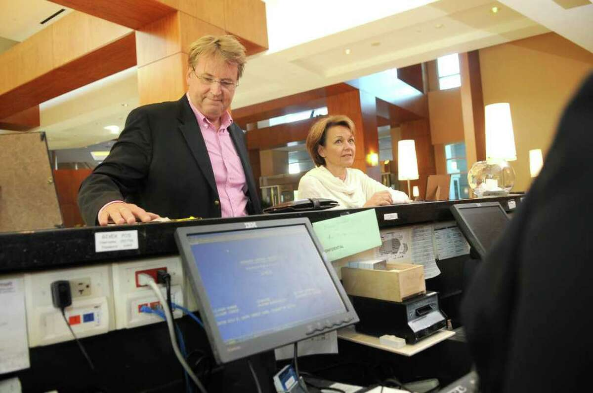 JERRY BAKER: FOR THE CHRONICLE CHECKING IN: Risto Neuvo, from left, and his wife, Eeva, of Pori, Finland, check in at the front desk of The Woodlands Waterway Marriott.