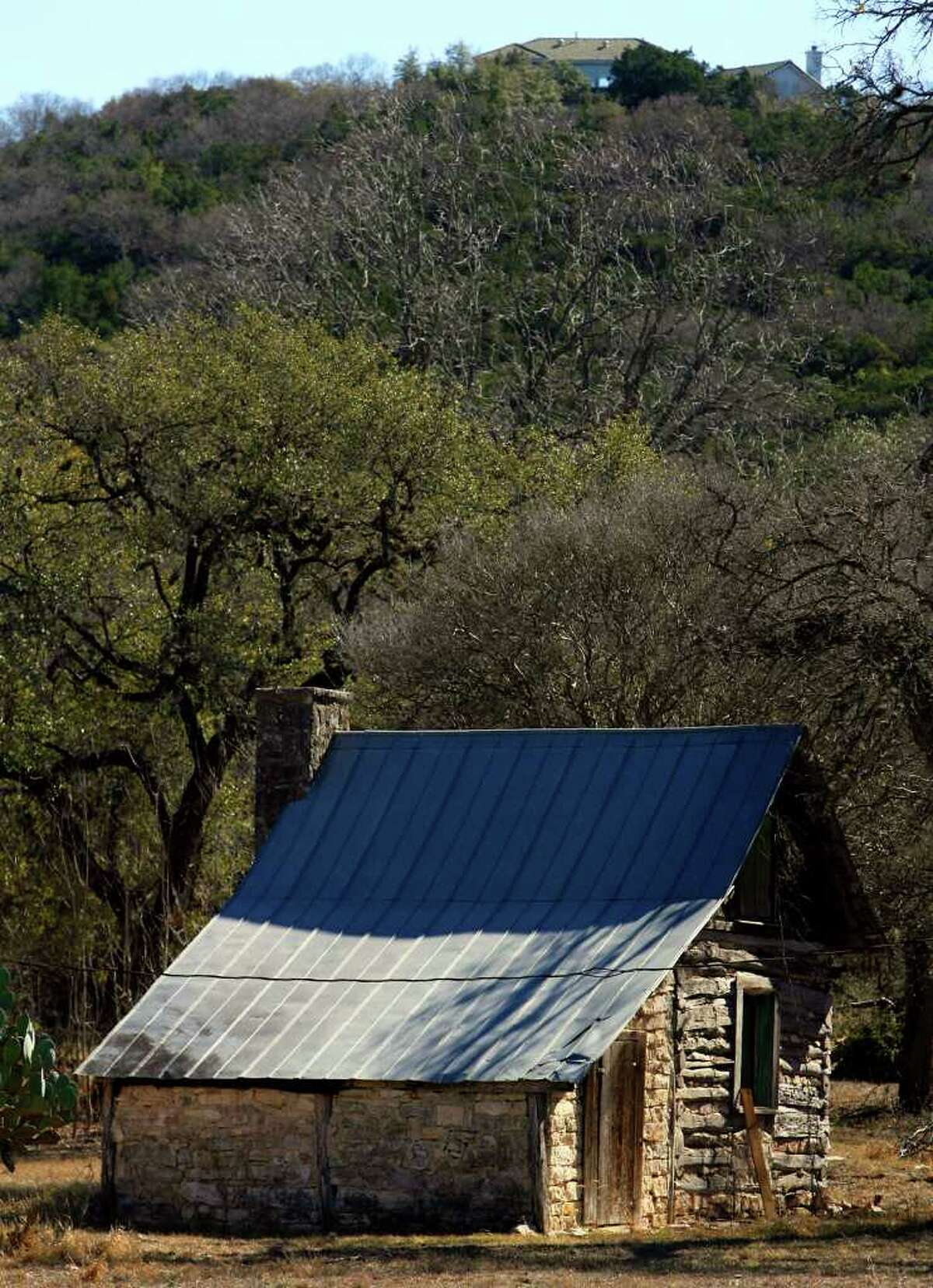 An old log cabin with a limestone addition is at the bottom of a hill on Boerne Stage Road. More modern structures are popping up on the top of the hill. JOHN DAVENPORT/jdavenport@express-news.net