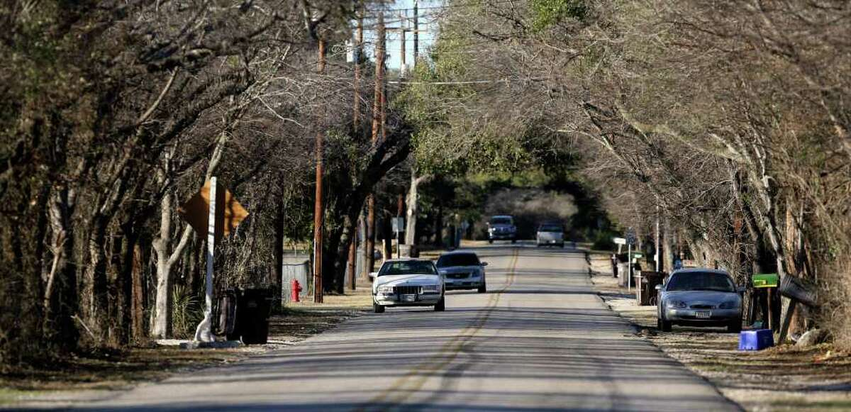 Cars travel down Scenic Loop Road in Grey Forest Wednesday. A canopy of trees shrouds the area. JOHN DAVENPORT/jdavenport@express-news