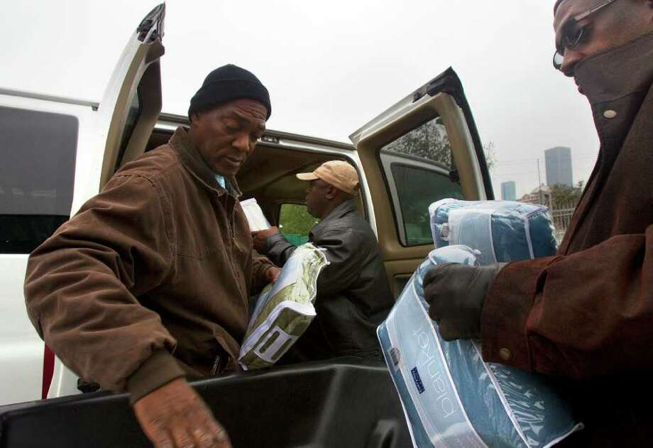 Cleveland Lee, left, Charles Williams, center, and Floyd Clark, right, load Star of Hope's Love-in-Action Van with blankets and sandwiches to help Houston's homeless combat the cold front coming to the area. Photo: Cody Duty, Houston Chronicle / © 2011 Houston Chronicle