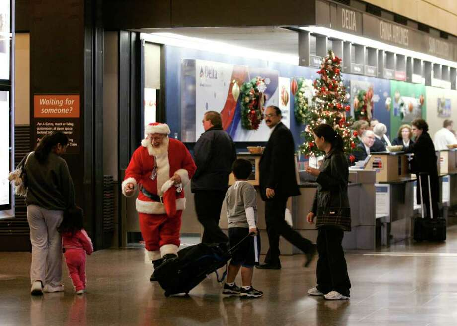 Dressed as Santa, Al Monson, a baggage handler with Northwest Airlines, hands out candy canes to children during his break at Seattle-Tacoma International Airport Monday, Dec. 11, 2006. Photo: Ted S. Warren, AP / AP