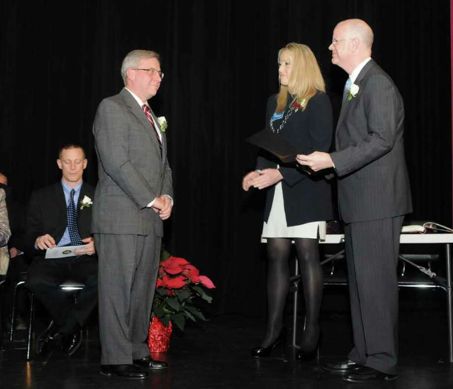 Matthew Knickerbocker, left, stands to be sworn in as the First Selectman of Bethel by Town Clerk Lisa Bergh and State of Connecticut Comptroller Kevin Lembo on Monday Dec. 5, 2011. The ceremonies took place at Bethel High School. Photo: Lisa Weir / The News-Times Freelance