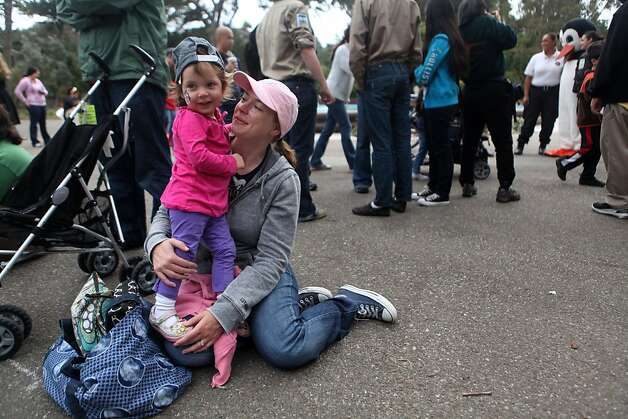 Krysta Pellegrino holds her daughter Mary as they wait for the penguin march at the San Francisco Zoo on Saturday. Photo: Audrey Whitmeyer-Weathers, The Chronicle