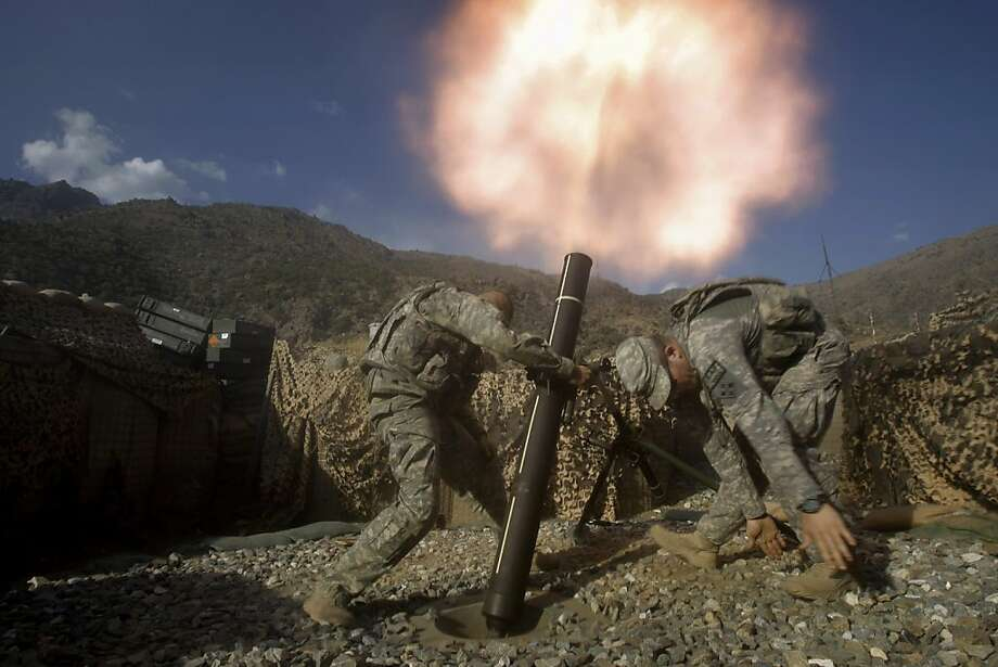 U.S. soldiers from the 2nd Battalion, 12th Infantry Regiment, 4th Brigade Combat Team, fire mortars at known enemy firing positions from a base in the Pech River Valley in Afghanistan's Kunar province, Saturday, Oct. 24, 2009. From left to right are SPC William Makenzie of Pendleton, OR and SPC Benjamin Pervis of Rochester, MN. Photo: David Guttenfelder, AP