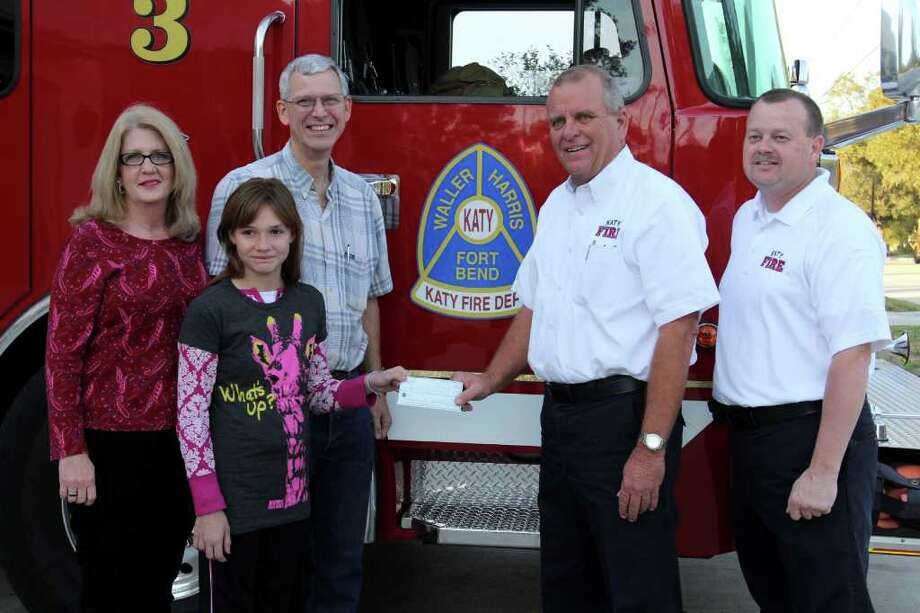 SUZANNE REHAK: FOR THE CHRONICLE HER FAVORITE THINGS: Mary Van Scyoc, 11, a fifth-grader at Hutsell Elementary, donated a check for $115 to the Katy Fire Department on Dec. 2 with money she raised from a garage sale two weeks ago. From left, are her parents, Brenda and Karl Van Scyoc, Mary; Marc Jordan, Katy fire chief, and Kenneth Redding, Katy assistant fire chief. Photo: Suzanne Rehak