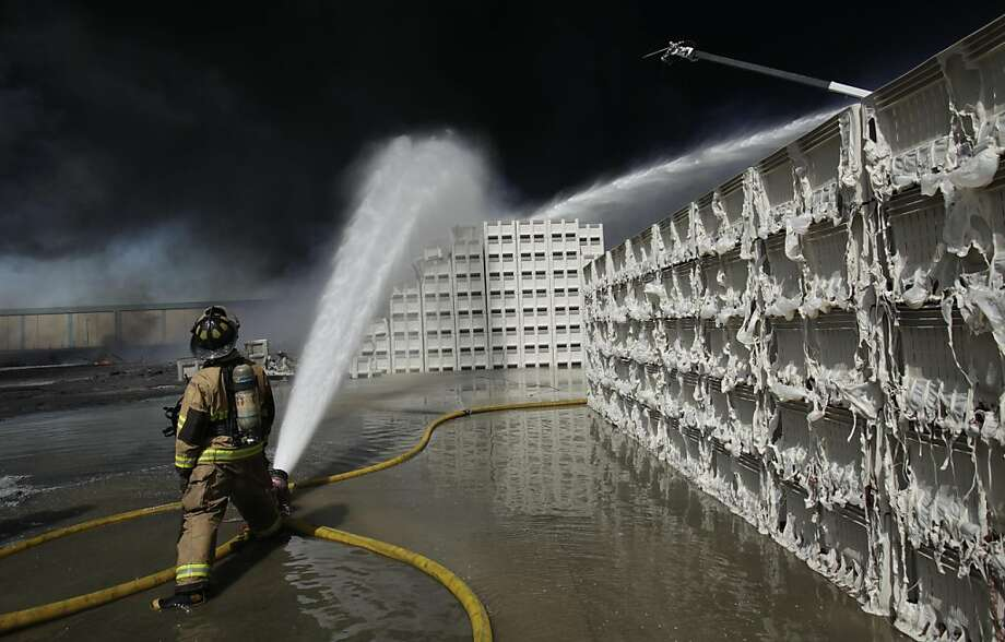 A fire fighter watches as water streams on plastic storage containers burning at a six-alarm fire at Macro Plastics in Fairfield,, Calif., Tuesday, July 26, 2011. No injuries have been reported in the fire. Photo: Rich Pedroncelli, AP