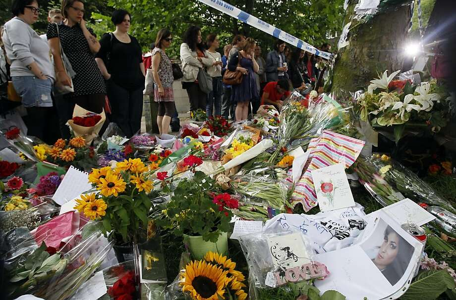 Fans gather around flowers and tributes near the home of British singer Amy Winehouse in London, Monday, July 25, 2011. Amy Winehouse, the beehived soul-jazz diva whose self-destructive habits overshadowed a distinctive musical talent, was found dead Saturday, July 23, 2011 in her London home. She was 27. Photo: Kirsty Wigglesworth, AP