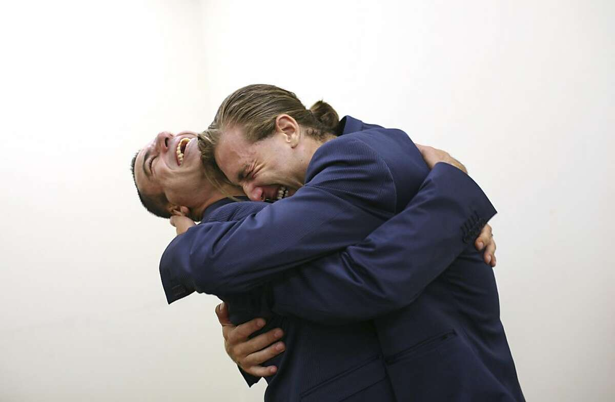 Lino Caminha-Strandquist, left, and Luke Strandquist-Caminha hug after exchanging vows at Manhattan's City Clerk's office on the first day of same-sex marriage in New York, July 24, 2011. Hundreds of gay and lesbian couples across New York State began marrying on Sunday in the culmination of a long battle in the Legislature and a new milestone for gay rights advocates seeking to legalize same-sex marriage across the nation. (Michael Appleton/The New York Times)