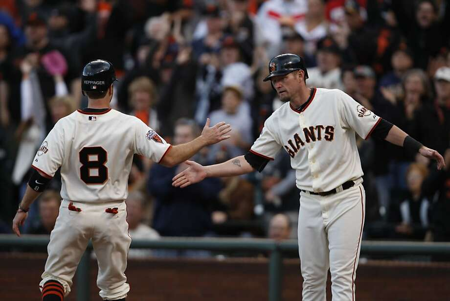 San Francisco Giants Aubrey Huff holds his hand out for teammate Jeff Keppinger as they both scored against the Milwaukee Brewers in San Francisco Calif.,  on July 23, 2011. Photo: Audrey Whitmeyer-Weathers, The Chronicle