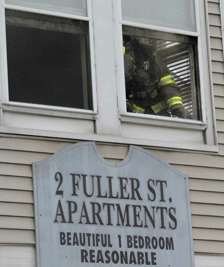 A Schenectady firefighter ventilates a second floor apartment during a smokey blaze at the 2 Fuller Street Apartments in Schenectady, N.Y. Dec. 6, 2011.  (Skip Dickstein / Times Union) Photo: SKIP DICKSTEIN / 2011