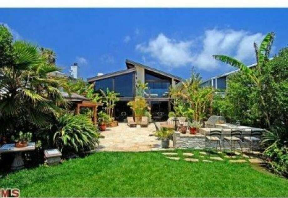 An external look at the home, spotlighting the beautiful green of the landscape. Photo: MLS