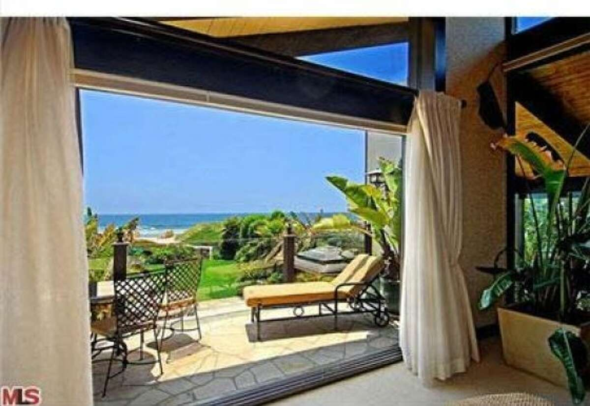 Looking out onto the patio of the house, the Pacific Ocean in the distance.