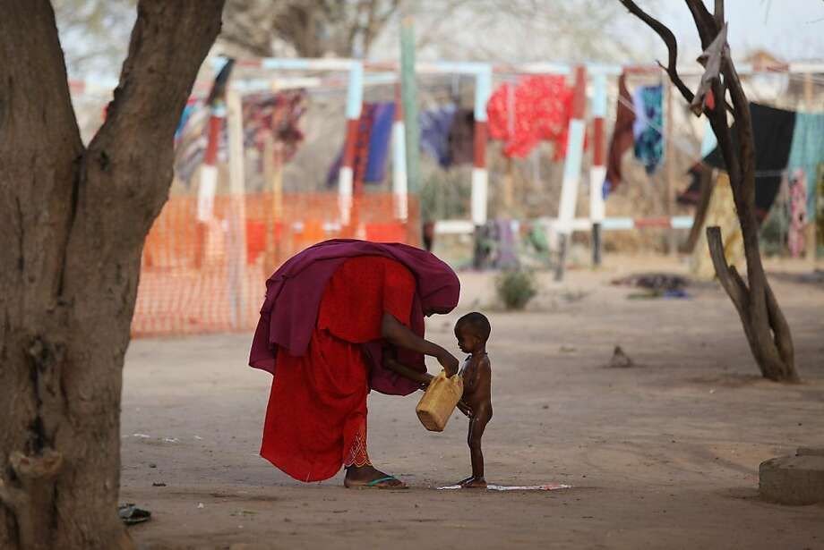 A mother washes her malnourished child in the Medecins Sans Frontieres Hospital in the Dagahaley refugee camp which makes up part of the giant Dadaab refugee settlement on July 22, 2011 in Dadaab, Kenya. The refugee camp at Dadaab, located close to the Kenyan border with Somalia, was originally designed in the early 1990s to accommodate 90,000 people but the UN estimates over 4 times as many reside there. The ongoing civil war in Somalia and the worst drought to affect the Horn of Africa in six decades has resulted in an estimated 12 million people whose lives are threatened. Photo: Oli Scarff, Getty Images